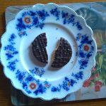 last biscuit broken in half on a plate with crumbs